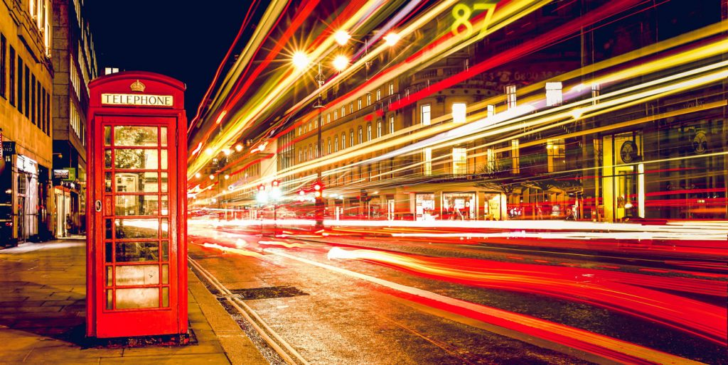Red telephone box at night with light trails of traffic